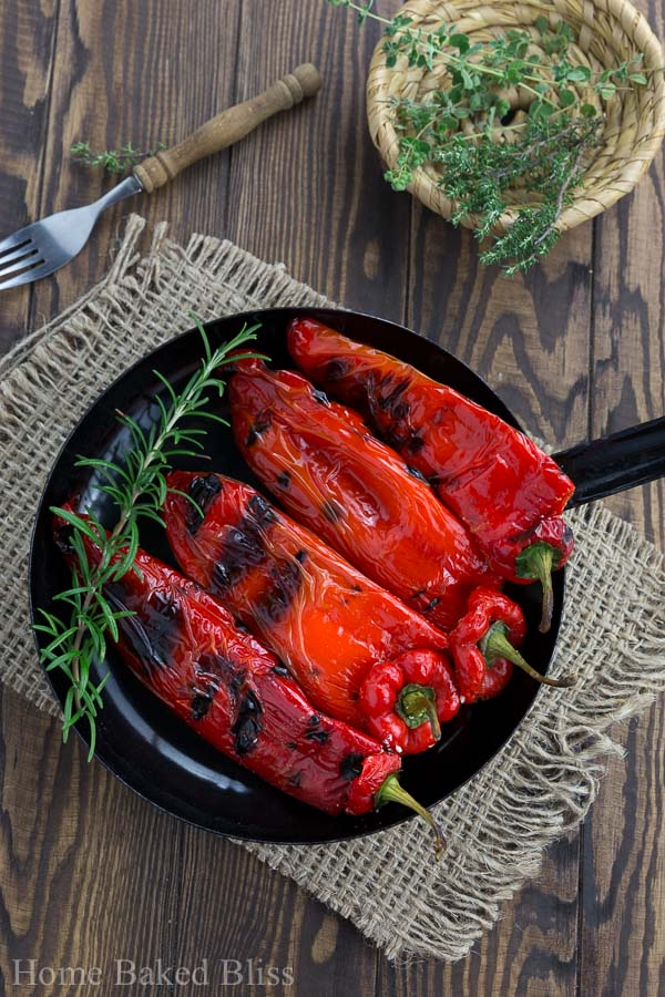 Grilled peppers with feta in a black pan next to to a bowl of herbs