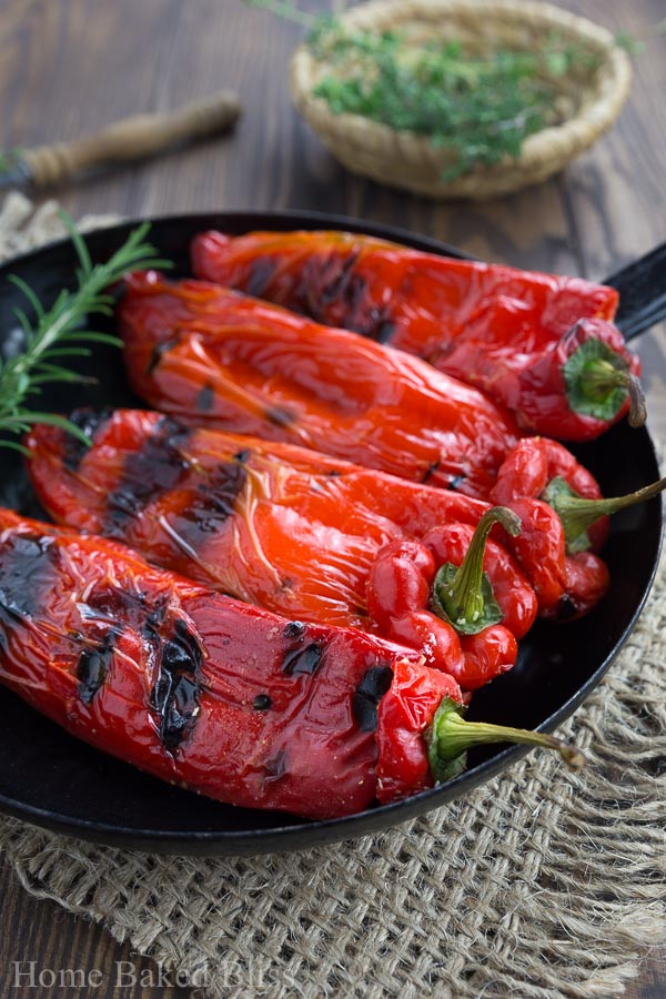 A closeup of the grilled peppers with feta in a black pan