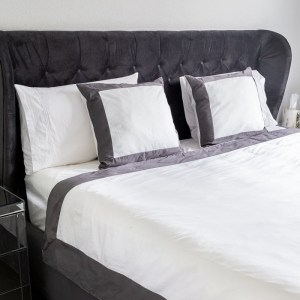 A tufted velvet bed in dark grey with grey and white bedding.