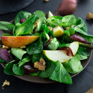Autumn salad with lambs lettuce, pears, onions and walnuts on a dark brown plate.