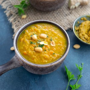 Two brown bowls with chunky carrot lentil curry soup.