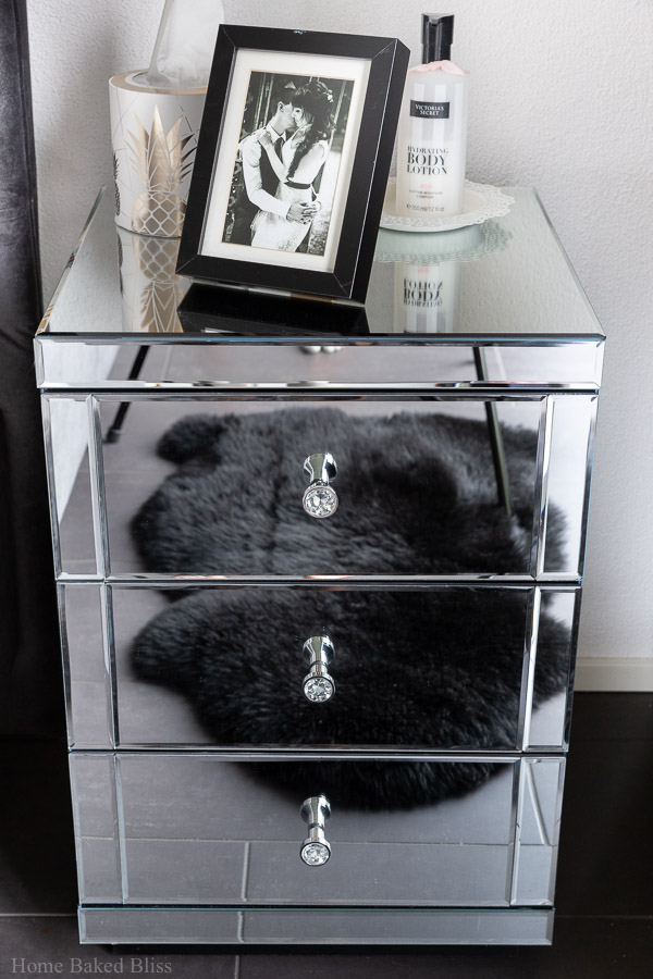 A mirror nightstand with a picture frame on top.