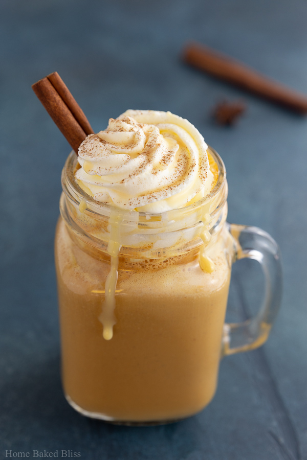 A pumpkin spice latte garnished with whipped cream and a cinnamon stick.