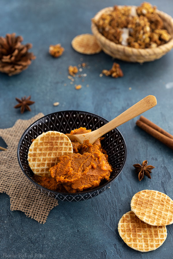 Pumpkin spice butter inside a bowl next to a cookie and wooden spoon.