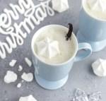 A cup of warm vanilla milk with a meringue kiss and vanilla bean garnish.