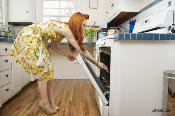 Side view of young woman opening oven door