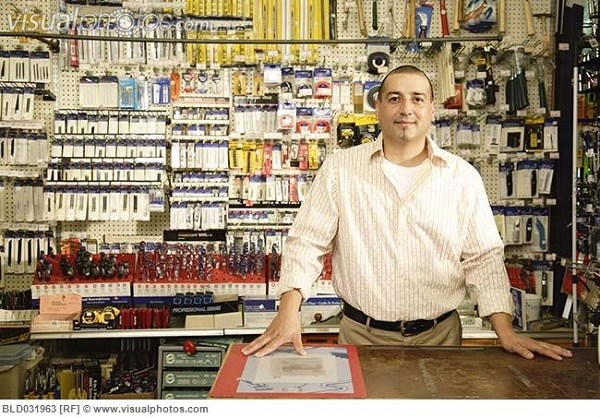 Hispanic man behind counter at hardware store