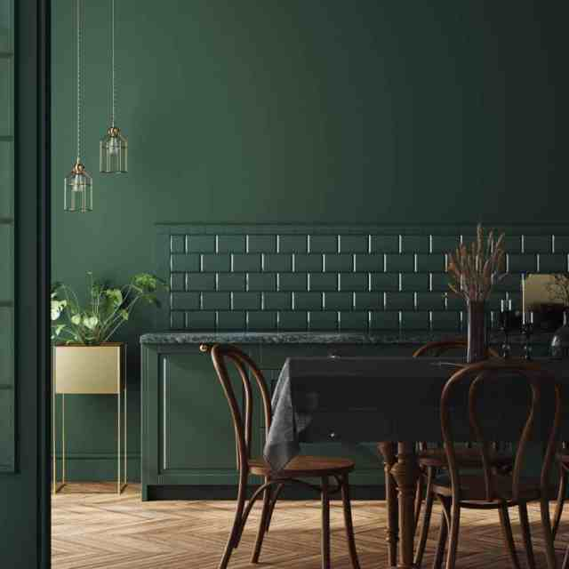 Koyu renkli ratan yemek sandalyeleri ve battaniyeli masa ile koyu yeşil temalı yemek alanı