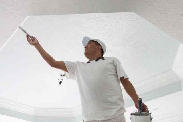 Ressam, yeniden dekore edilen bir evin yatak odasındaki kesonlu tavanı boyuyor