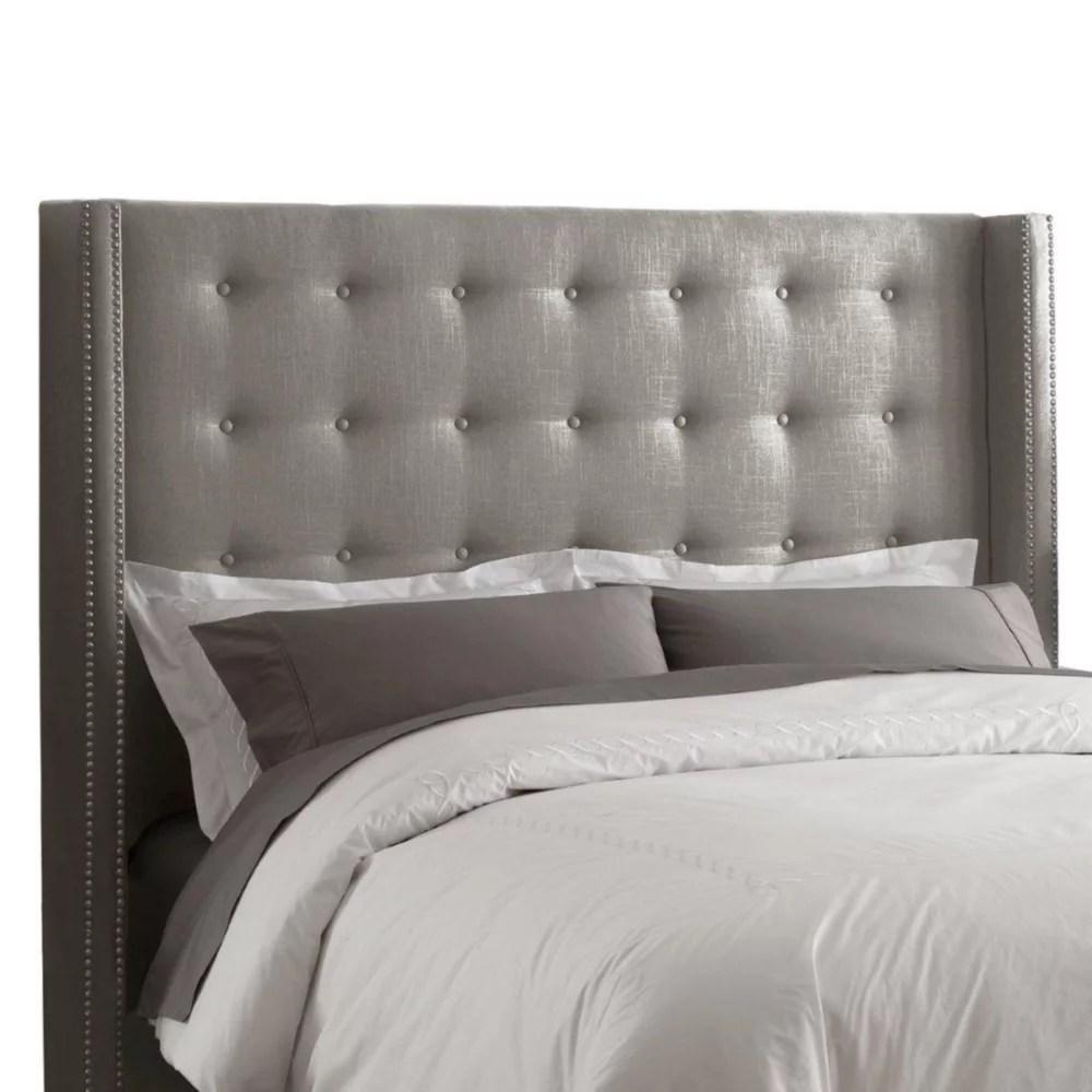 tete de grand lit capitonnee en lin de ton gris enjolivee de tetes de clous en etain