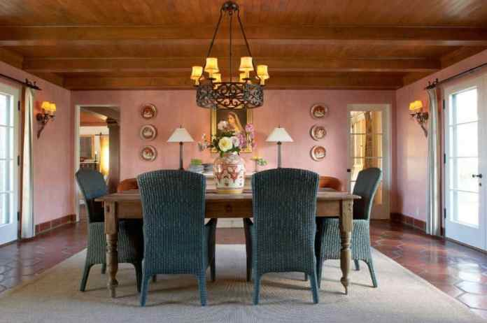 The traditional wooden ceiling that has exposed wooden beams matches with the rustic rectangular wooden table matched with rustic green woven wicker chairs augmented by a terracotta flooring that is contrasted by the pink walls.