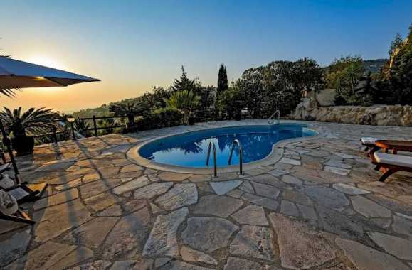A Small Pool On Cliffside Property With A Massive Flagstone Patio That Takes Up The Entire Backyard