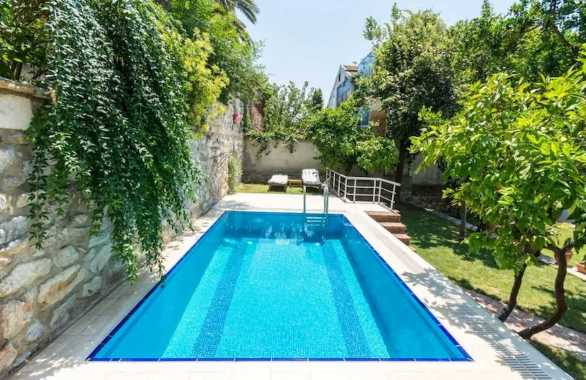 Rectangle Outdoor Swimming Pool Surrounded By Gardens And Trees