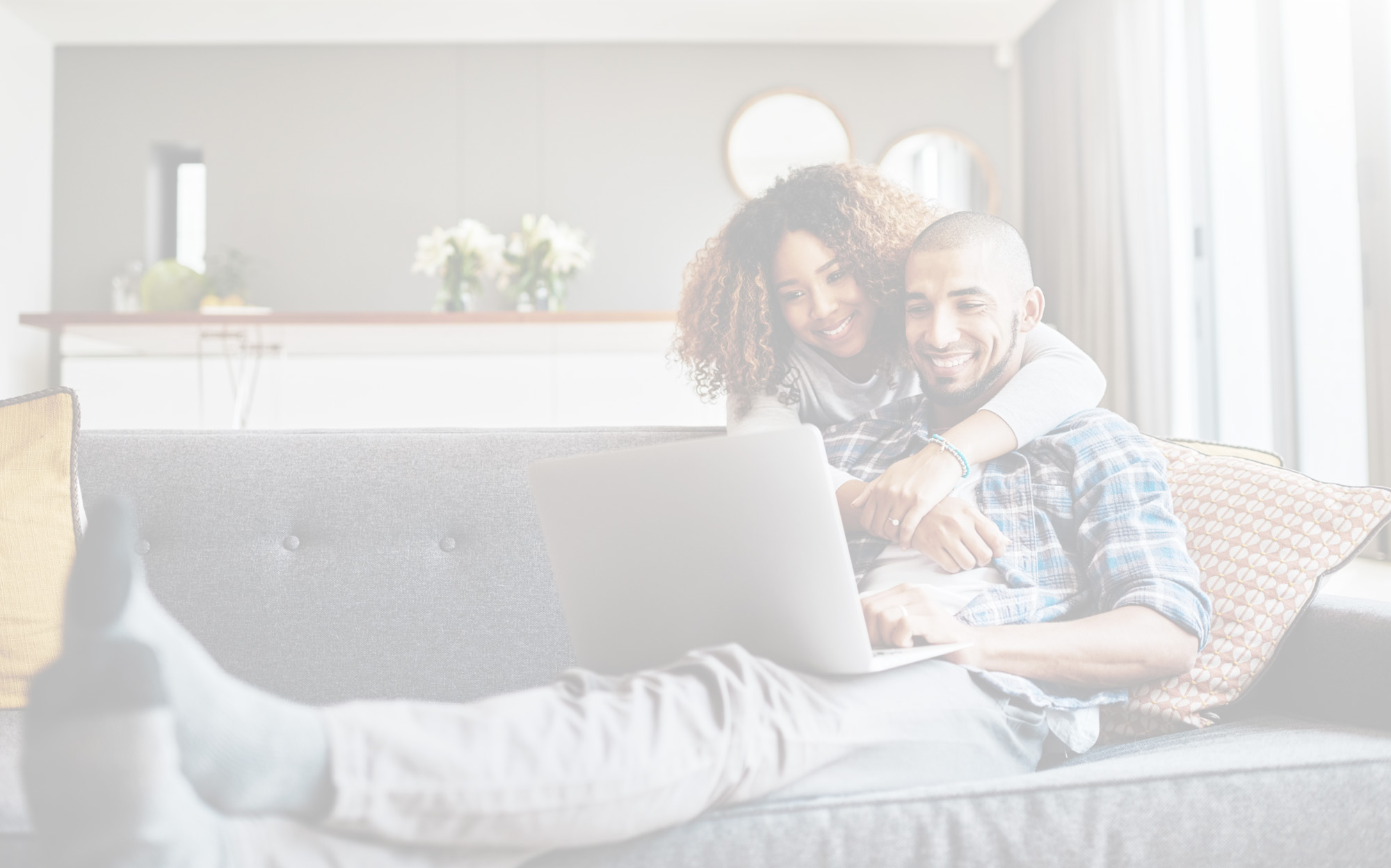 photo of couple sitting on couch looking at a computer