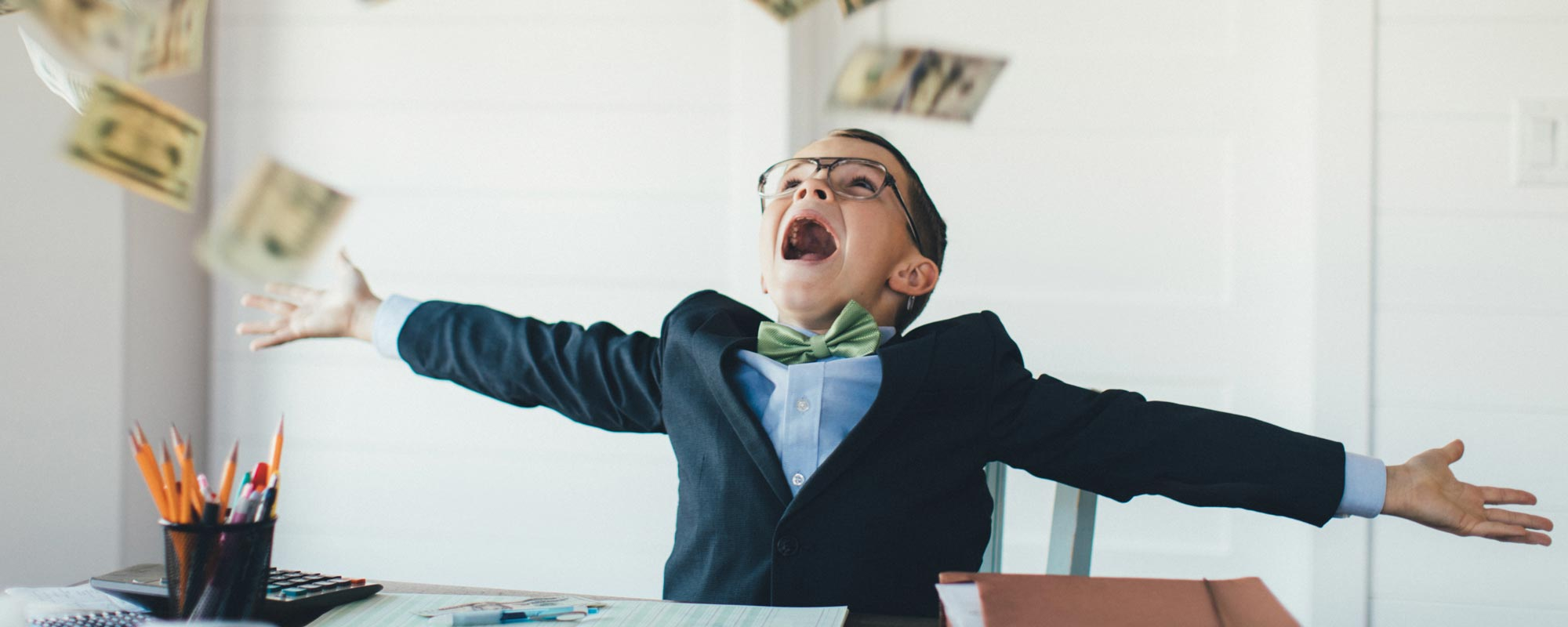creative photo of boy dressed in a suite sitting at a desk throwing money in the air