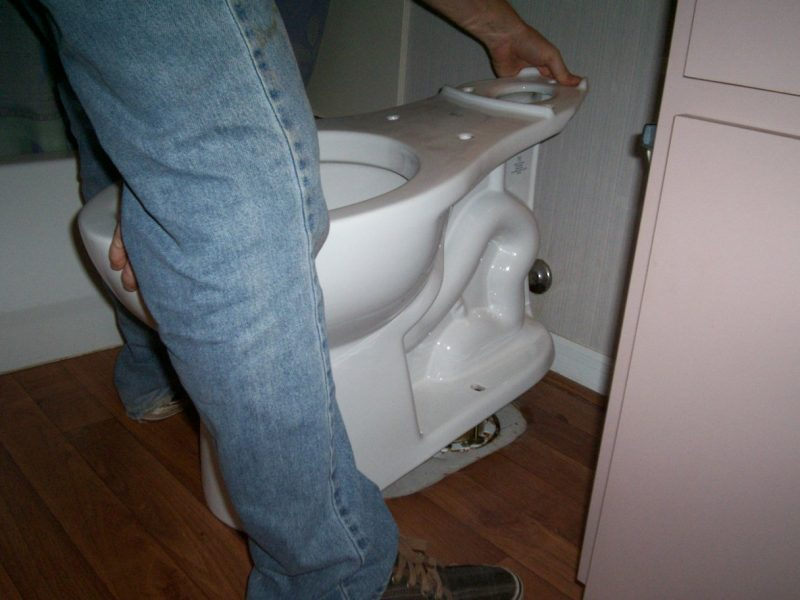 Carefully setting the new toilet onto the wax ring and flange