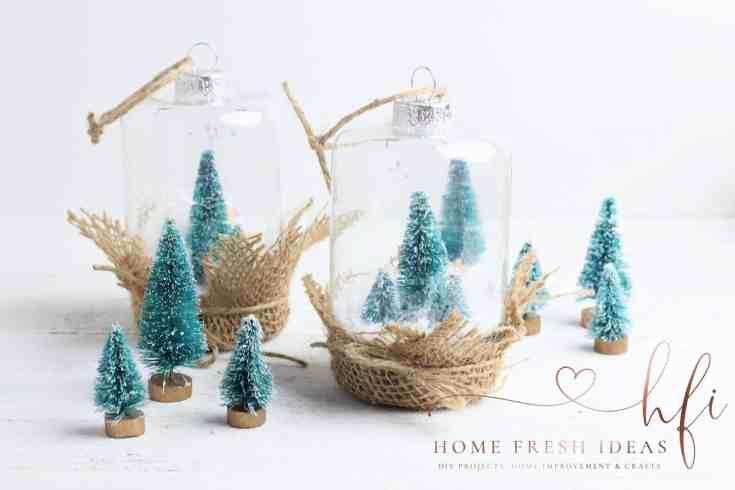 2 Christmas snow globes with mini trees around