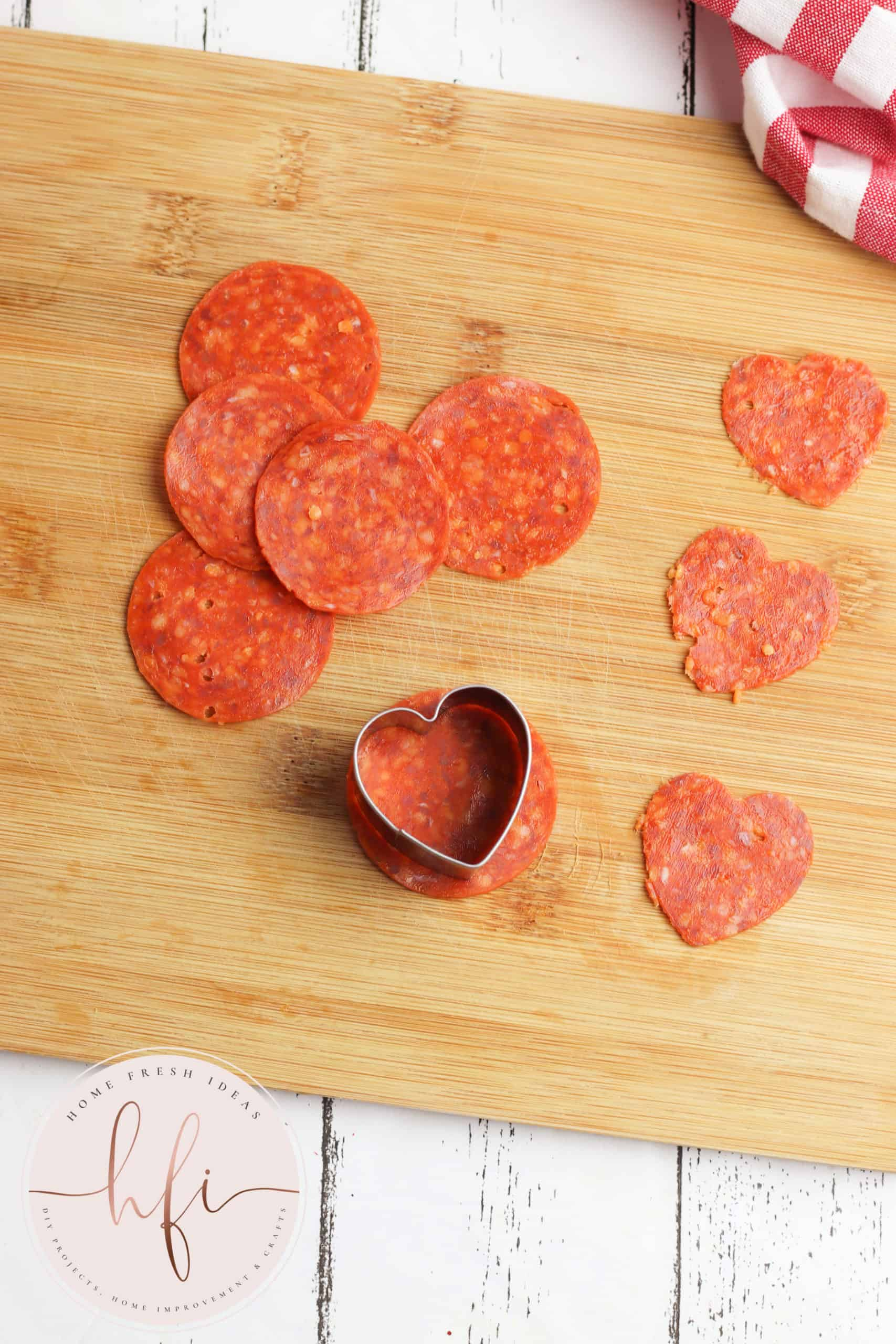 cutting heart shapes out of pepperoni