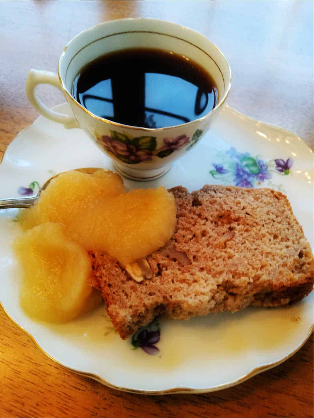 walnut applesauce bread on a plate with coffee