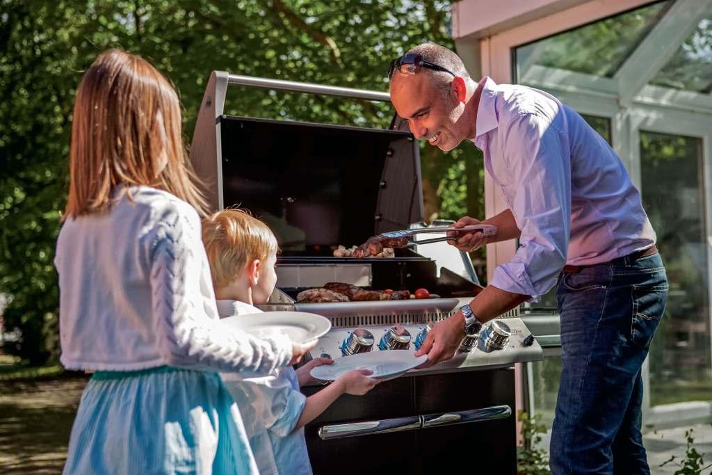 Foto: man met twee kinderen bij een grill van Napoleon. De foto hoort bij de 10 tips voor bbq-seizoen 2018.