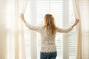 17592196 - woman looking out big bright window with curtains and blinds