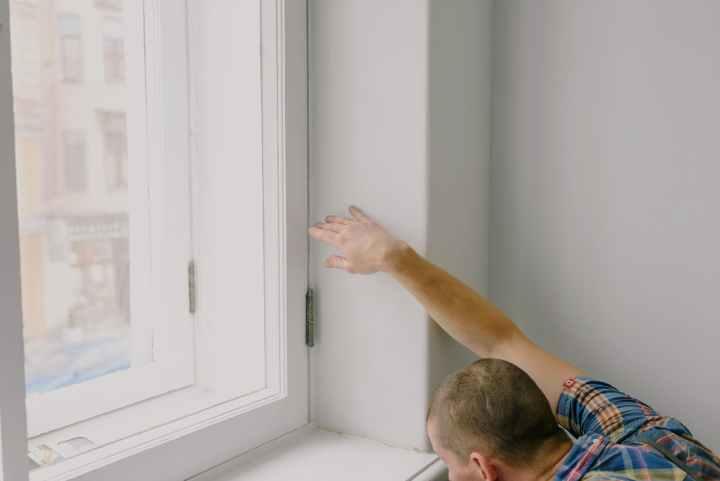 بازرس خانه در حال چک کردن پنجره ها برای تهیه گزارش بازرسی فنی