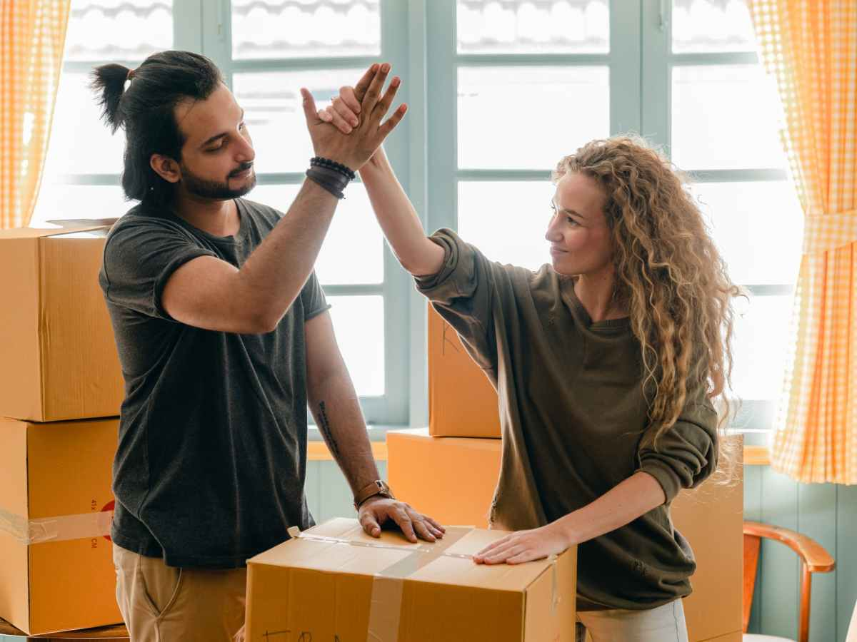 multiracial couple giving high give standing near pile of boxes