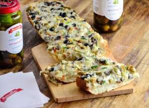 Sliced Olive Cheese Bread on a wooden werving board.