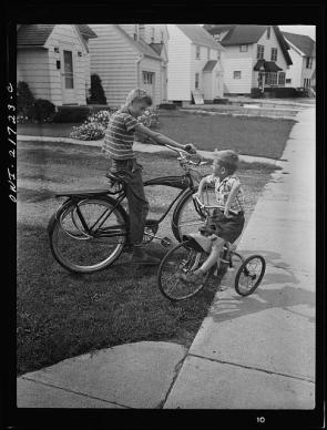 Howard and Earl Babcock playing in front of their house with their cycles