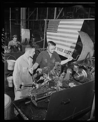 Mr. Babcock explaining an operation to one of the men whom he supervises at the plant