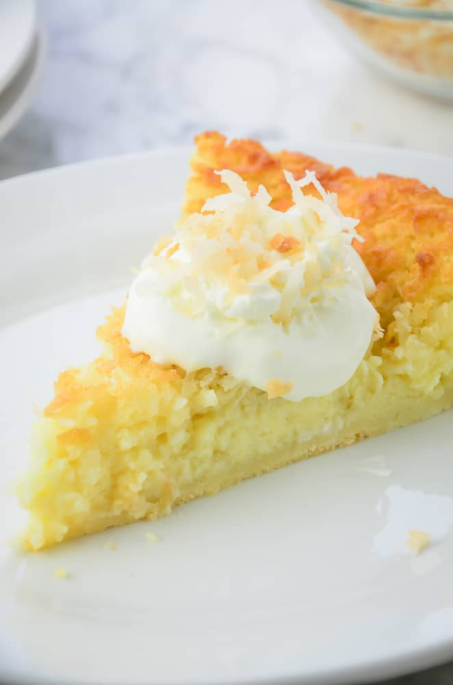 Close up of Impossible coconut pie topped with whipped cream and toasted coconut