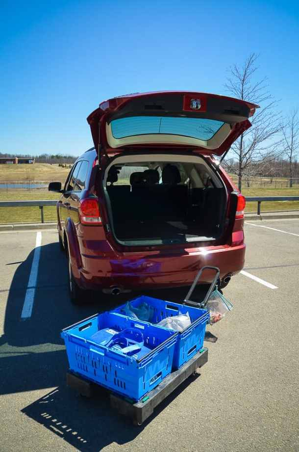 car with trunk open in walmart grocery pick up area, groceries on cart in blue bins. #shop #Smithfield #GetGrillingAmerica #CollectiveBias