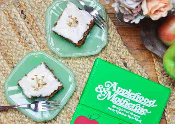 Two slices of Apple Spice cake on jade plates with forks  on a wooden table sitting next to a bowl of apples and the Applehood and Motherpie Cookbook