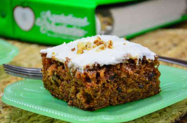 A slice of apple spice cake with cream cheese frosting on a jade plate sitting in front of the cookbook Applehood and Motherpie