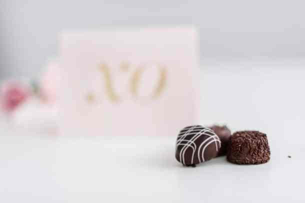 3 chocolates on a white table with valentines day card in background