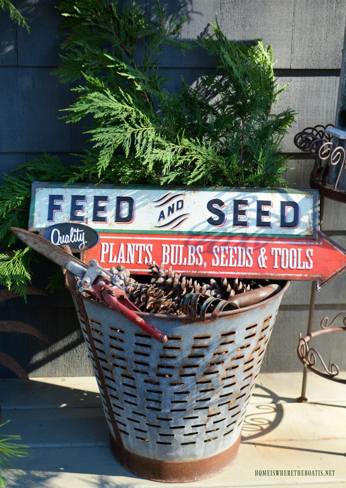 Olive bucket with greenery, pine cones, vintage garden tools and Feed and Seed Sign | ©homeiswheretheboatis.net
