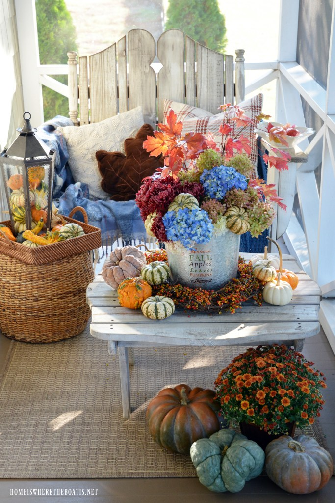 Autumn harvest arrangement and fall on the porch with pumpkins, mums, leaves and bittersweet vine | ©homeiswheretheboatis.net #falll #porch