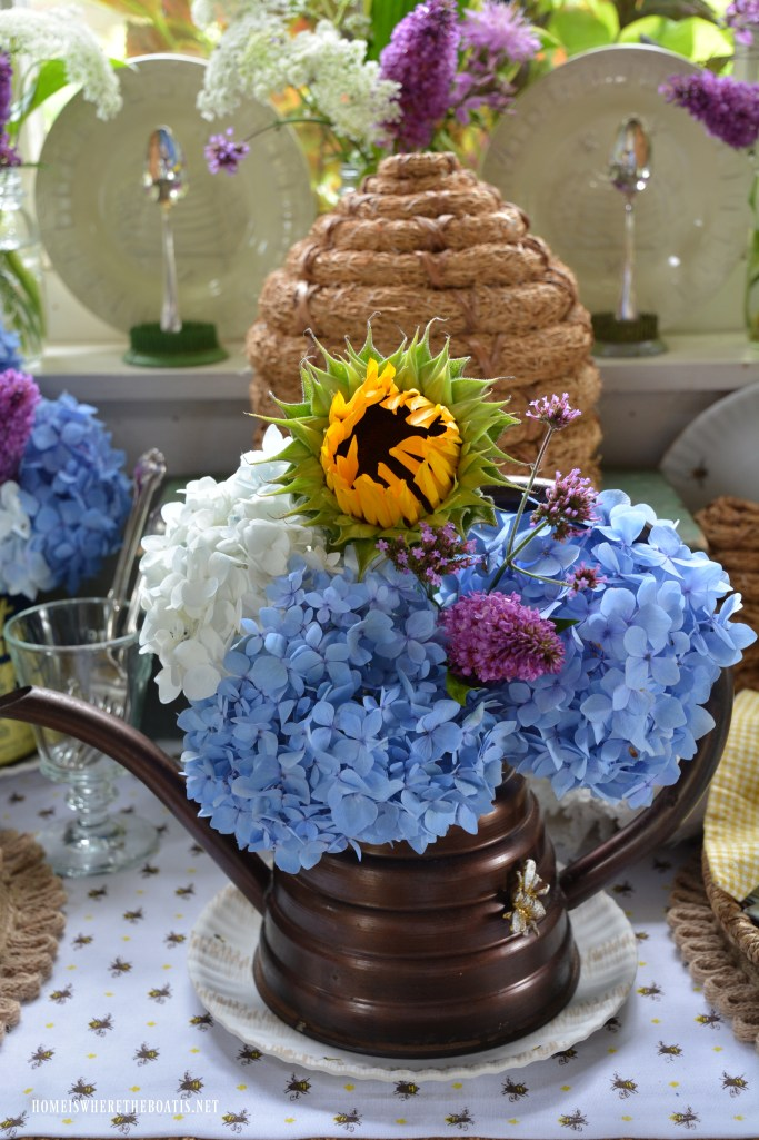 Beehive watering can with flowers and table for National Pollinator Week | ©homeiswheretheboatis.net #bees #tablescapes #wateringcan #hydrangeas