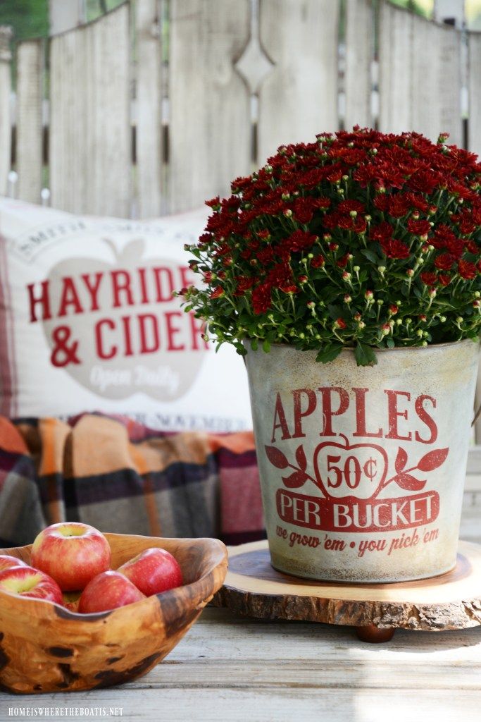 Mums in apple bucket and Apples on the Porch | ©homeiswheretheboatis.net #fall #porch #apples