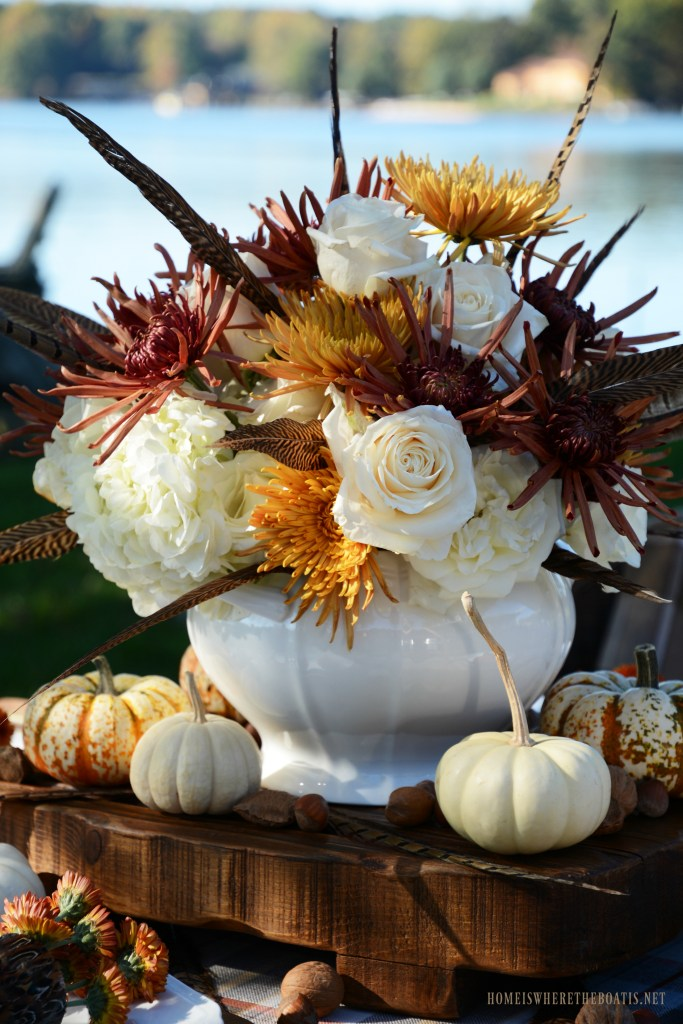 Fall flower arrangement centerpiece with roses, hydrangeas, mums and feathers | ©homeiswheretheboatis.net #fall #tablescape #alfresco #flowers #feathers