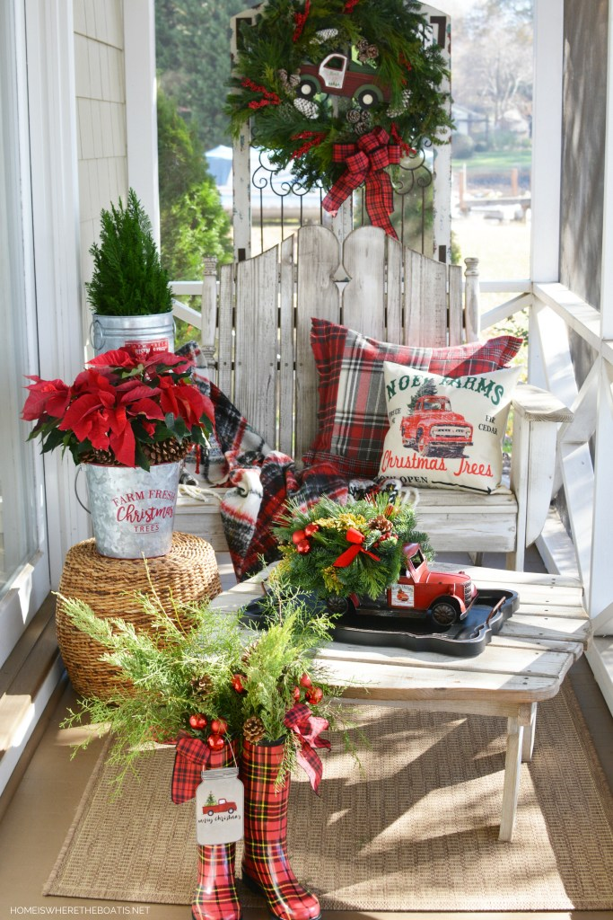 Christmas on the porch with truck centerpiece, greenery, wreath and wellies | ©homeiswheretheboatis.net #christmas #truck #centerpiece