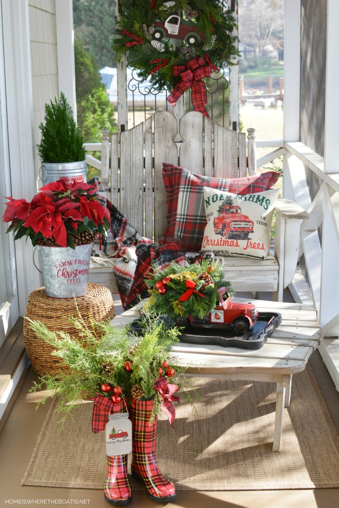 Christmas on the porch with truck centerpiece, greenery and wellies | ©homeiswheretheboatis.net #christmas #truck #centerpiece