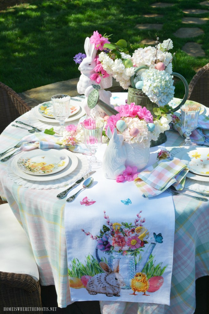 Alfresco table with a blooming watering can, butterflies and bunny and chick with eggs for Easter | ©homeiswheretheboatis.net