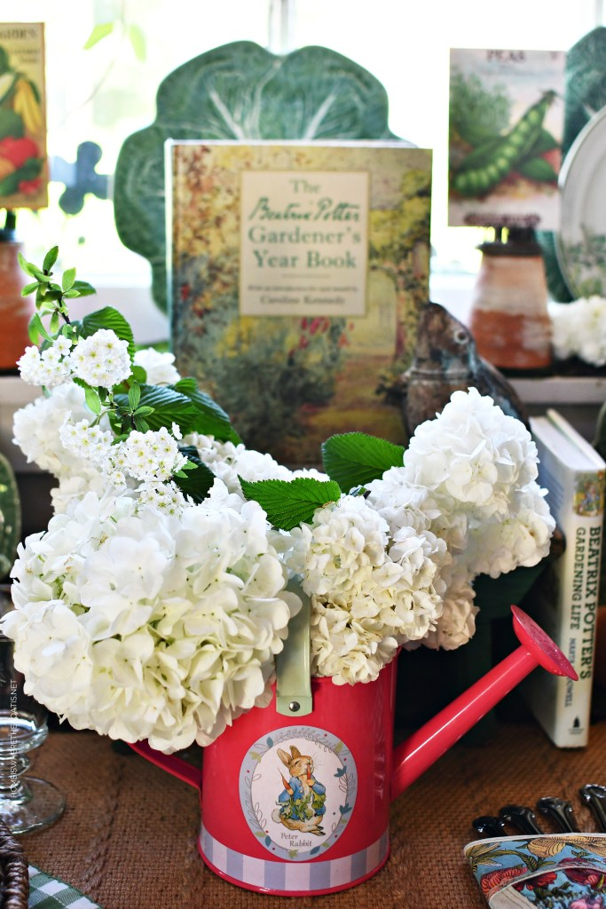 Peter Rabbit watering can with viburnum blooms | ©homeiswheretheboatis.net #spring #garden #tablescapes #peterrabbit