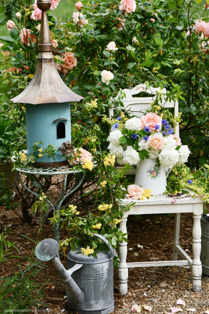 Birdhouse, watering can and pitcher with garden flowers | ©homeiswheretheboatis.net #garden #flowers #spring #arrangement #roses