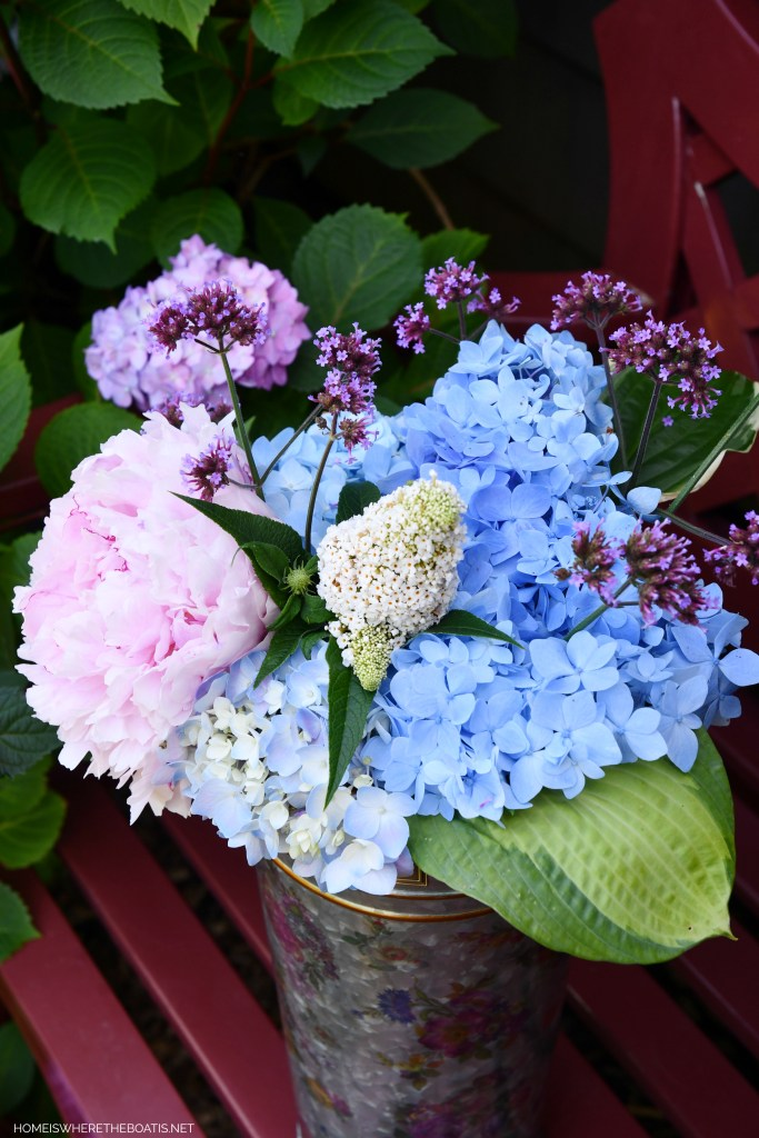 Flower market bucket with hydrangeas, butterfly bush, peony, verbena and hosta | ©homeiswheretheboatis.net #flowers #garden #hydrangeas