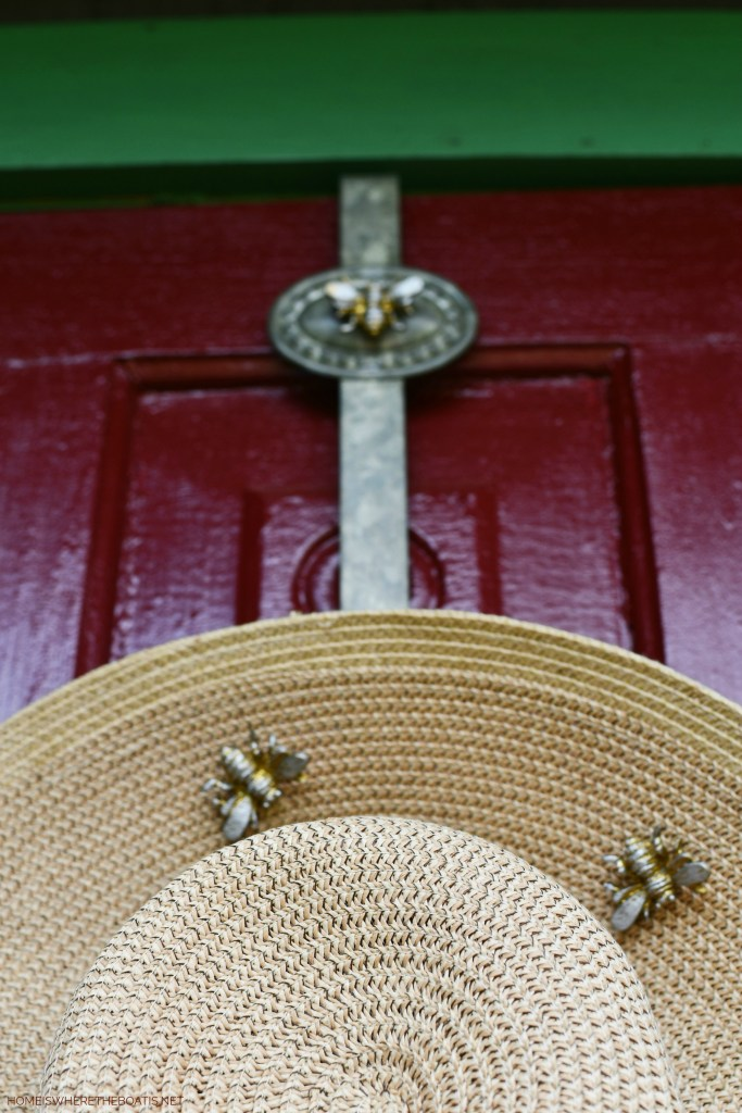 Straw hat with bees and door decor for Potting Shed | ©homeiswheretheboatis.net #bees #flowers #garden #shed