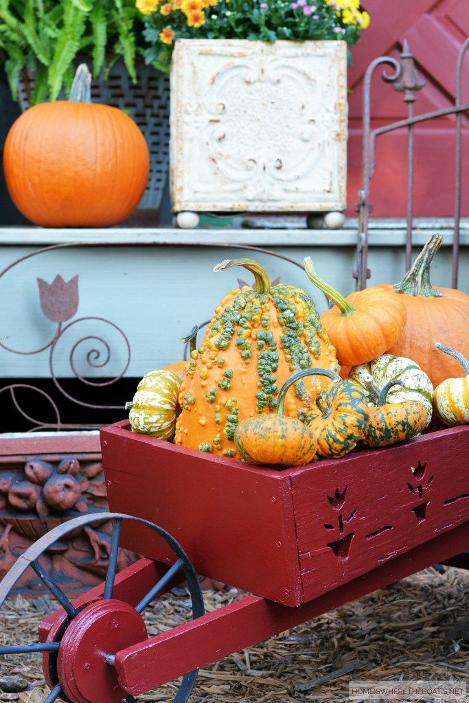 Wheelbarrow of Pumpkins and Hello Autumn Potting Shed | ©homeiswheretheboatis.net #fall #shed #pumpkins