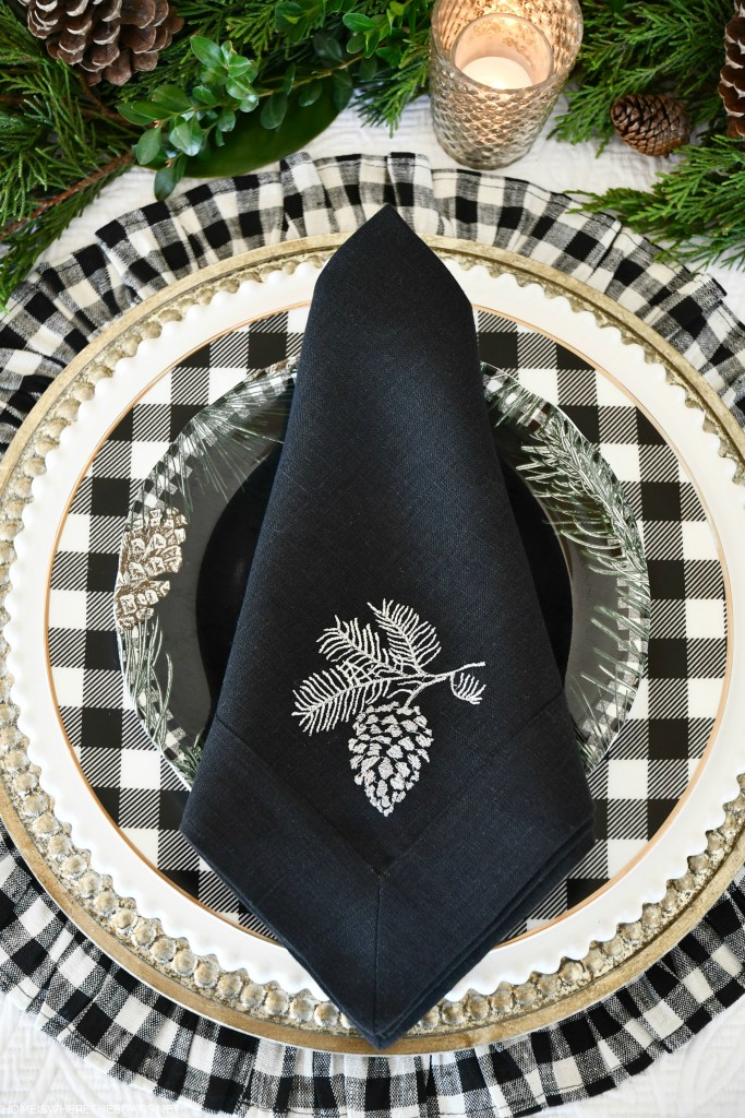 Christmas tablescape with Crown Linen Designs pinecone napkins, evergreen runner and black and white checked placemats | ©homeiswheretheboatis.net #christmas #tablescapes