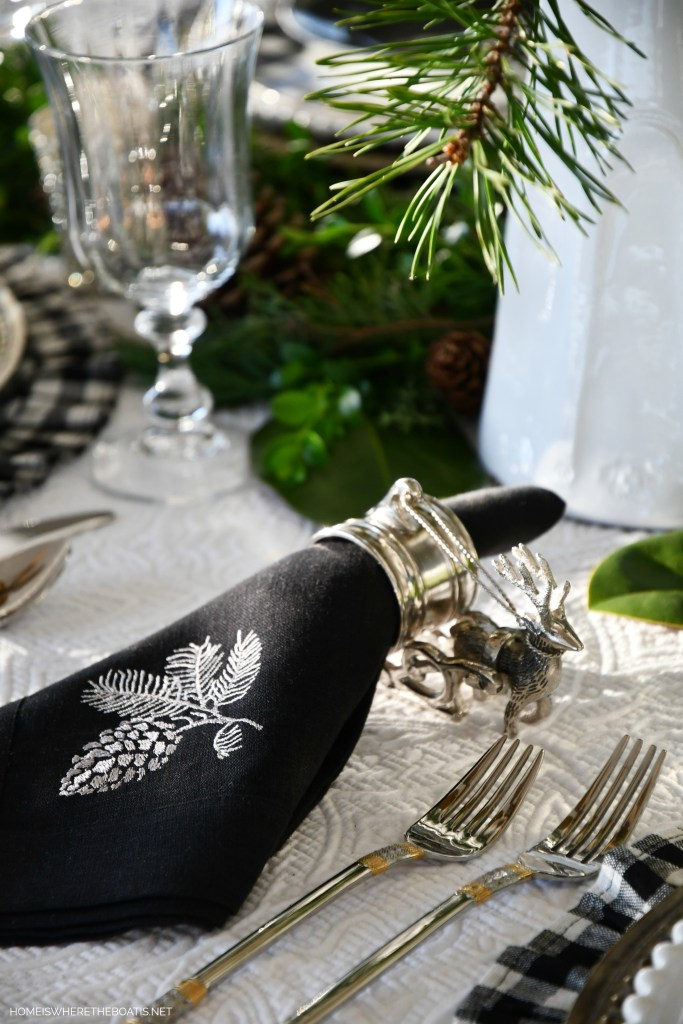 Christmas tablescape with evergreen runner, deer plates and black and white checks | ©homeiswheretheboatis.net #christmas #tablescapes